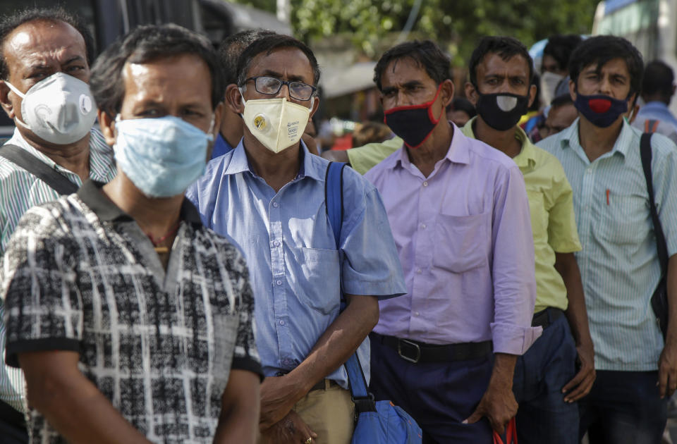 Commuters with face masks wait in a queue at a bus station in Kolkata, India, Friday, July 17, 2020. India crossed 1 million coronavirus cases on Friday, third only to the United States and Brazil, prompting concerns about its readiness to confront an inevitable surge that could overwhelm hospitals and test the country's feeble health care system. (AP Photo/Bikas Das)