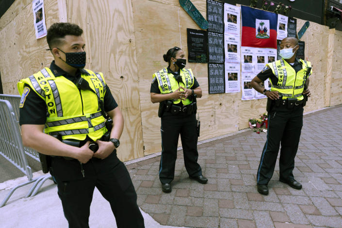 FILE - In this June 6, 2020, file photo, Boston Police officers stand in front of messages about George Floyd posted on a boarded-up business in Downtown Crossing in Boston. The city's police department remains largely white, despite vows for years by city leaders to work toward making the police force look more like the community it serves. Advocates say Black and Latino candidates still consistently get passed over in favor of white applicants. (AP Photo/Michael Dwyer, File)