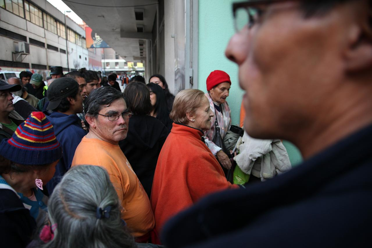 """In this May 24, 2013 photo, Ana Luisa Villarroel, 78, center right, waits in line to be one of the first to enter the homeless shelter at the indoor stadium Estadio Victor Jara in Santiago, Chile. This is her first night at the shelter after she left what she described as an abusive situation at her family's home. This emblematic stadium, which hosts sporting events throughout the year, was where Chilean folk singer Victor Jara was tortured and killed on Sept. 14, 1973, just days after the military coup. """"For me, it's a miracle to be here where they are now giving shelter and food to everyone and where they killed Victor Jara,"""" said Ana Luisa Villaroel, 78, who lived through the dictatorship. (AP Photo/Brittany Peterson)"""