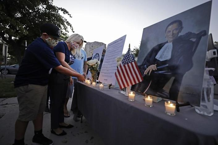SAN PEDRO, CA - SEPTEMBER 21: Shannon Ross, president of the San Pedro Democratic Club and organizer of the candlelight vigil, lights a candle with her son Luke, 12, at the end of a vigil for Ruth Bader Ginsburg at the Port of Los Angeles Liberty Hill Plaza on Monday, Sept. 21, 2020 in San Pedro, CA. (Myung J. Chun / Los Angeles Times)