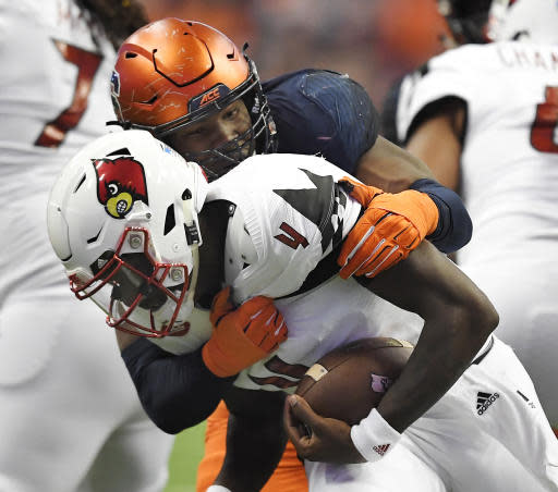 FILE - In this Nov. 9, 2018, file photo, Syracuse defensive lineman Alton Robinson, top, sacks Louisville quarterback Jawon Pass during the second half of an NCAA college football game in Syracuse, N.Y. The Orange finished 2018 with 18 interceptions and 13 fumble recoveries, the most turnovers of any Power Five team in the nation. Syracuse returns stalwart defensive ends Alton Robinson and Kendall Coleman, who combined for 20 of the Orange's 43 sacks (10 apiece). (AP Photo/Adrian Kraus, File)