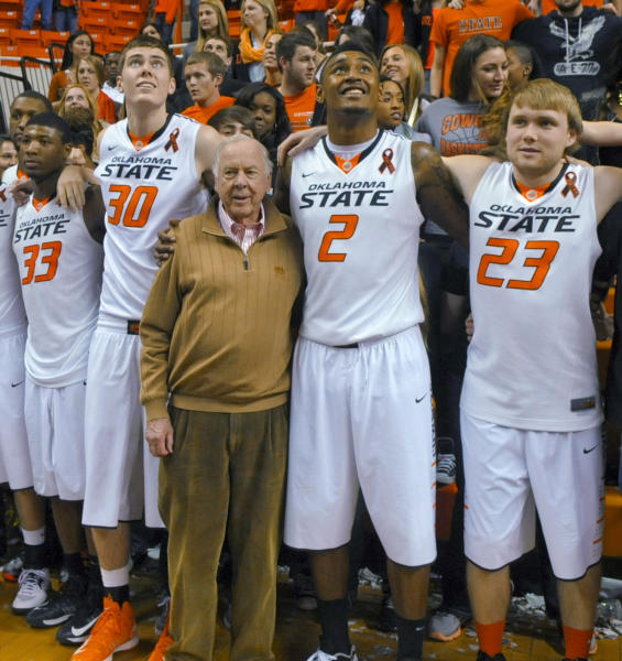 FILE - In this March 2, 2013, file photo, oil tycoon and Oklahoma State supporter T. Boone Pickens, center, celebrates with Oklahoma State's basketball team members Marcus Smart (33), Mason Cox (30), Le'Bryan Nash (2) and Alex Budke, right, following the team's win over Texas in an NCAA college basketball game in Stillwater, Okla. Pickens, a brash and quotable oil tycoon who grew even wealthier through corporate takeover attempts, died Wednesday, Sept. 11, 2019. He was 91. (AP Photo/Brody Schmidt, File)