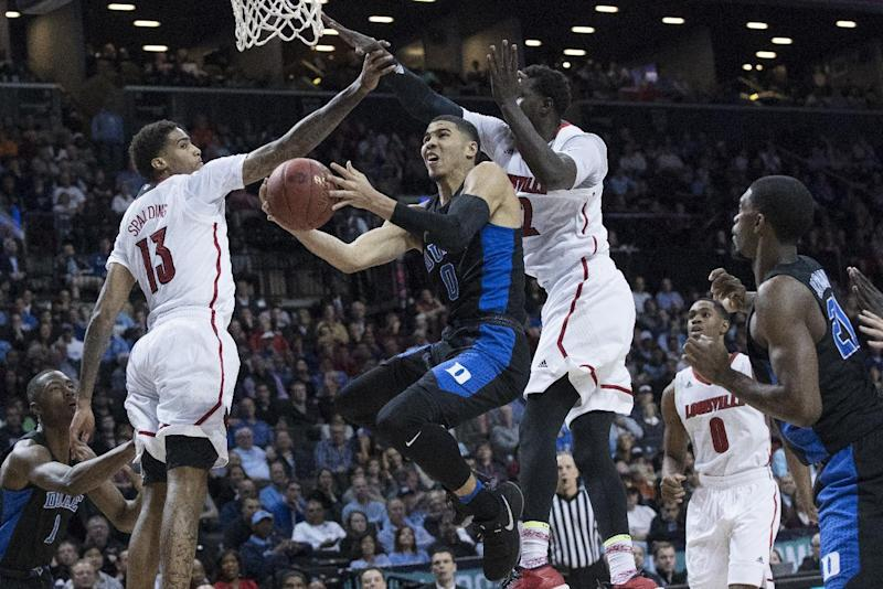 Duke forward Jayson Tatum (0) goes to the basket against Louisville forward Ray Spalding (13) and forward Mangok Mathiang during the first half of an NCAA college basketball game in the Atlantic Coast Conference tournament, Thursday, March 9, 2017, in New York. (AP Photo/Mary Altaffer)