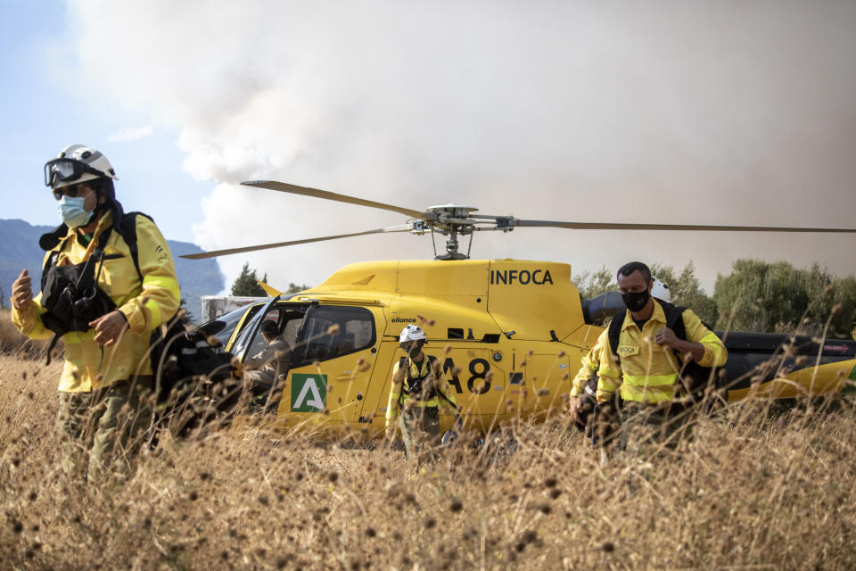 Forest firefighters work in a wildfire in Estepona, Spain, Thursday, Sept. 9, 2021. Nearly 800 people have been evacuated from their homes and road traffic has been disrupted as firefighting teams and planes fight a wildfire in southwestern Spain. (AP Photo/Sergio Rodrigo)