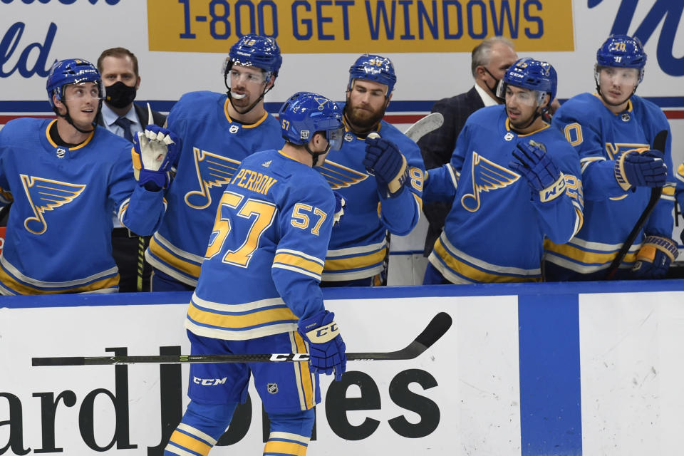 St. Louis Blues' David Perron (57) is congratulated by teammates after scoring a goal against the Los Angeles Kings during the second period of an NHL hockey game Saturday, Jan. 23, 2021, in St. Louis. (AP Photo/Joe Puetz)