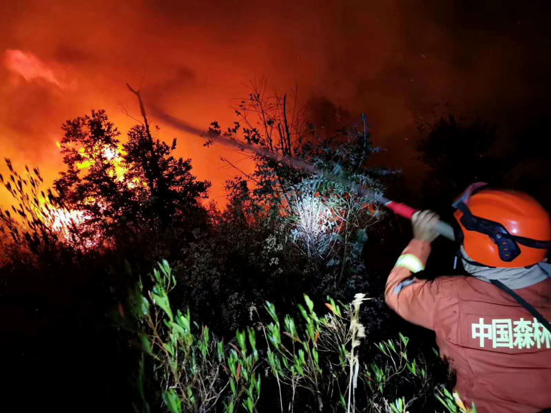 In this Monday, March 30, 2020 photo, a firefighter battles a forest fire as it approaches a gas station in Xichang in southwestern China's Sichuan Province. More than a dozen of people have died while fighting a raging forest fire in southwestern China and reinforcements were sent to fight the blaze and evacuate nearby residents, officials and state media reported Tuesday. (Chinatopix via AP)
