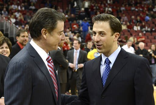 Louisville coach Rick Pitino, left, shakes hands with his son Richard Pitino, right, coach of Florida International, before their NCAA college basketball game on Wednesday, Dec. 19, 2012, in Louisville, Ky. (AP Photo/Timothy D. Easley)