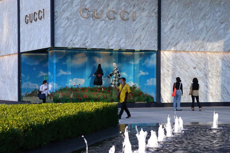 People wearing face masks following the COVID-19 outbreak walk past a store of Italian luxury brand Gucci at a shopping complex in Beijing