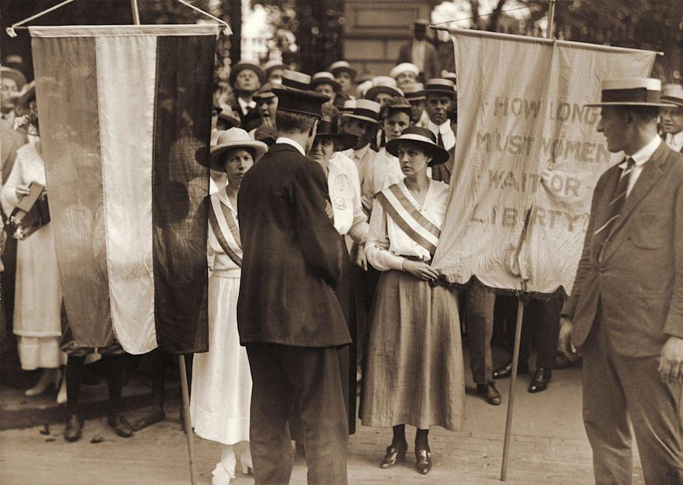 """<p>A protesting suffragette held up a sign asking, """"How long must women wait for liberty?""""</p>"""