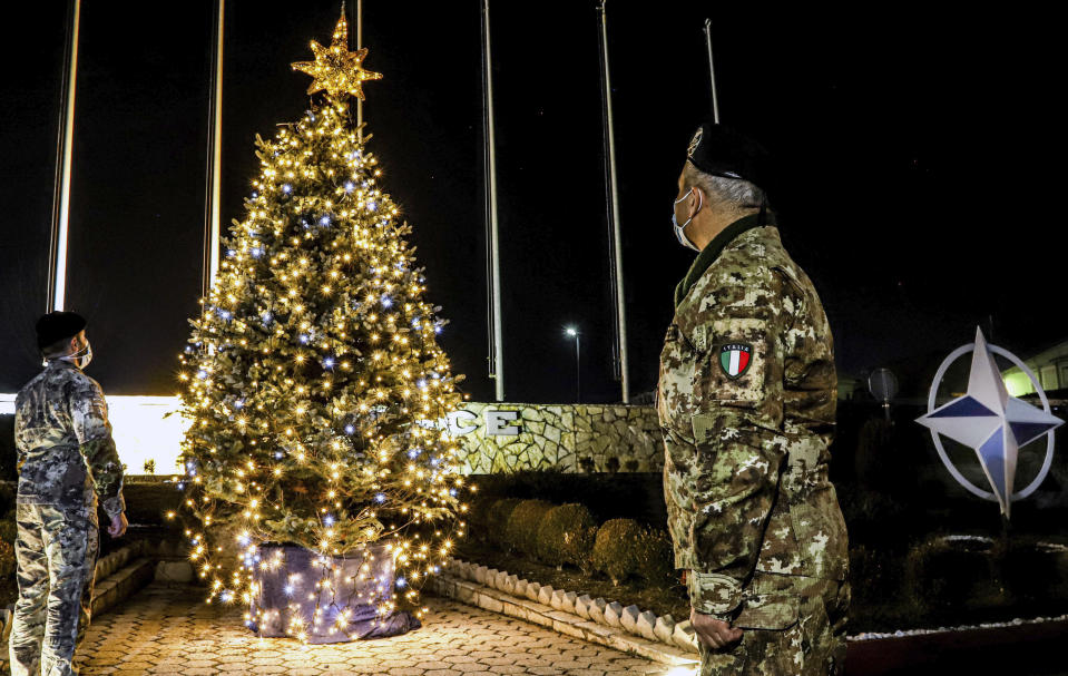 In this photo provided by NATO-led peacekeeping mission in Kosovo (KFOR), Italian soldiers watch Christmas tree on the Christmas Eve in the KFOR military headquarters in Kosovo capital Pristina, Thursday, Dec. 24, 2020. The coronavirus pandemic has totally changed Christmas time operation method and celebrations for the Kosovo Force but it has left unchanged its mission: keeping Kosovo safe and secure for 22 years now on. (KFOR via AP)