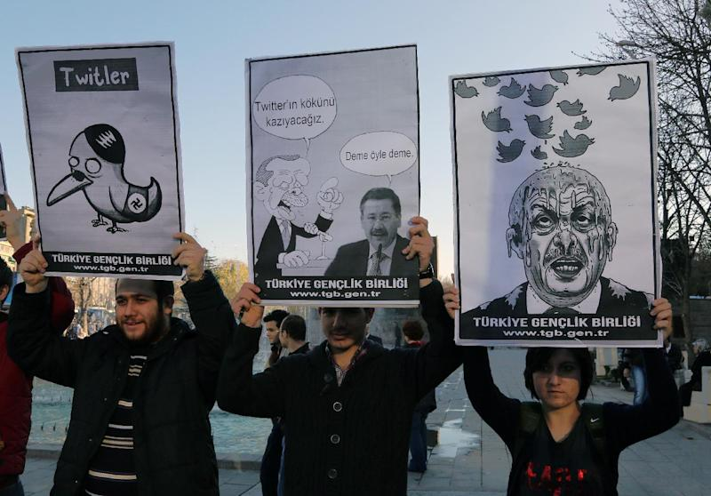 "Members of the Turkish Youth Union hold cartoons depicting Turkey's Prime Minister Recep Tayyip Erdogan during a protest against a ban on Twitter, in Ankara, Turkey, Friday, March 21, 2014. Turkey's attempt to block access to Twitter appeared to backfire on Friday with many tech-savvy users circumventing the ban and suspicions growing that the prime minister was using court orders to suppress corruption allegations against him and his government. Cartoon in center reads: Erdogan, left, to his Ankara Mayor Melih Gokcek "" we will rip out the roots of Twitter."" Gokcek: ""don't say it."" (AP Photo/Burhan Ozbilici)"