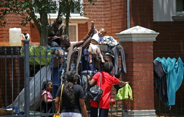 Several hundred asylum-seekers scaled the iron railings of the United Nations High Commissioner for Refugees office in Pretoria seeking protection (AFP Photo/Phill Magakoe)