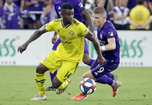 Columbus Crew's Waylon Francis (14) moves the ball around Orlando City's Chris Mueller (9) during the first half of an MLS soccer match Saturday, July 13, 2019, in Orlando, Fla. (AP Photo/John Raoux)
