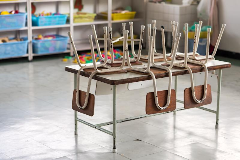 Old chairs on table with many blurred toys and study equipments of kindergarten room. empty classroom without any student. End of school semester concept. (Photo: blanscape via Getty Images)