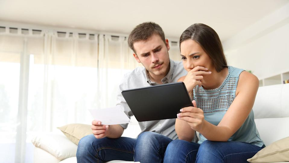 Worried couple checking bank account online in a tablet sitting on a couch in the living room at home