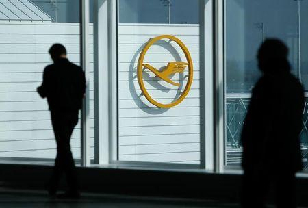 Traveller walk past a sign of German airline Lufthansa before the company's annual news conference in Munich