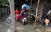 Villagers move to a safer place from the flooded area of Hatisela in Kamrup district of Assam. (Photo credit should read Anuwar Ali Hazarika/Barcroft Media via Getty Images)