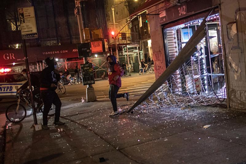 People run out of a smoke shop that they broke into as police arrive on the scene on Monday, June 1, 2020, in New York. Protests were held throughout the city over the death of George Floyd, a black man in police custody in Minneapolis who died after being restrained by police officers on Memorial Day. (AP Photo/Wong Maye-E)
