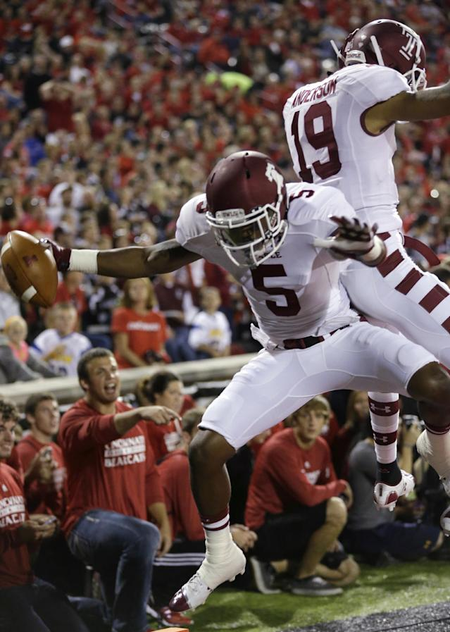 Temple's Jalen Fitzpatrick (5) celebrates with Robbie Anderson (19) after Fitzpatrick scored on a 35-yard touchdown reception in the first half of an NCAA college football game against Cincinnati, Friday, Oct. 11, 2013, in Cincinnati. (AP Photo/Al Behrman)