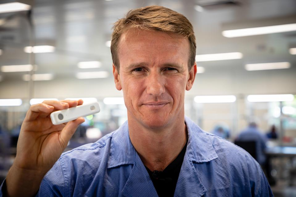 In this picture taken on December 21, 2020, Sean Parsons, founder and CEO of Australian digital diagnostics company Ellume, poses with a COVID-19 coronavirus home test unit that has been granted Emergency Use Authorization (EUA) by the US Food and Drug Administration (FDA), at the company's production facility in Brisbane. - Ellume's product delivers results in just 15 minutes and will soon be available over the counter in pharmacies across the country worst-hit by the pandemic. (Photo by Patrick HAMILTON / AFP) / To go with AFP story Health-virus-test-Australia-US, FOCUS by Holly Robertson (Photo by PATRICK HAMILTON/AFP /AFP via Getty Images)