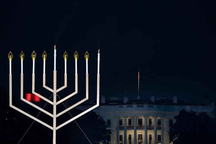 The White House is seen behind the newly lit National Menorah during a ceremony in President's Park just south of the White House on 10 December, 2020 (Getty Images)