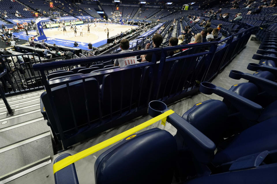 Seats are marked for social distancing at an NCAA college basketball game in the Southeastern Conference tournament Wednesday, March 10, 2021, in Nashville, Tenn. Large buildings with high ceilings and ventilation systems that can change out fresh air almost a third as well as airplanes are reasons why experts and engineers believe it's reasonable for limited numbers of fans to be returning to live, indoor sporting events. They say masks are still necessary, but most professional and big college arenas like the ones that host NHL and NBA games and the NCAA Tournament have the capacity to make it work and keep people from spreading the coronavirus. (AP Photo/Mark Humphrey)