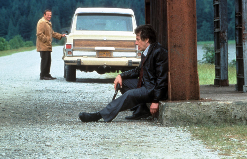 Robin Williams watches as Al Pacino sits on the side of the road in a scene from the film 'Insomnia', 2002. (Photo by Warner Brothers/Getty Images)
