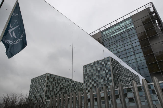 The flag of the International Criminal Court is reflected in a mirrored wall of the building in The Hague, Netherlands, Wednesday, Jan. 16, 2019, where lawyers were scheduled to discuss the next steps in the case of Gbagbo and ex-youth minister Charles Ble Goude, a day after both men were acquitted of crimes against humanity. (AP Photo/Peter Dejong)