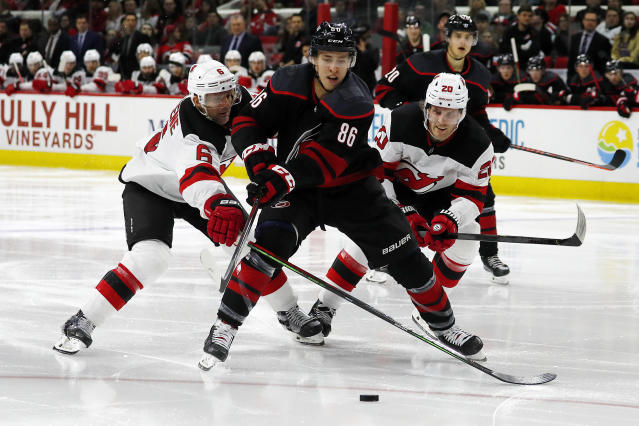 Carolina Hurricanes' Teuvo Teravainen (86), of Finland, splits the defense of New Jersey Devils' Andy Greene (6) and Blake Coleman (20) during the second period of an NHL hockey game in Raleigh, N.C., Friday, Feb. 14, 2020. (AP Photo/Karl B DeBlaker)