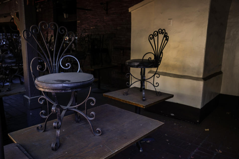 Dusty chairs are placed on top of dining tables in the patio area of a shuttered restaurant on Olvera Street in downtown Los Angeles, Tuesday, Dec. 15, 2020. Olvera Street, known as the birthplace of Los Angeles, has been particularly hard hit by the coronavirus pandemic, with shops and restaurants closed and others barely hanging on. (AP Photo/Jae C. Hong)