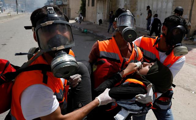 <p>A female Palestinian medic is evacuated after inhaling tear gas fired by Israeli forces during a protest against the U.S. Embassy's move to Jerusalem and ahead of the 70th anniversary of Nakba, near Ramallah in the occupied West Bank on May 14, 2018. (Photo: Mohamad Torokman/Reuters) </p>