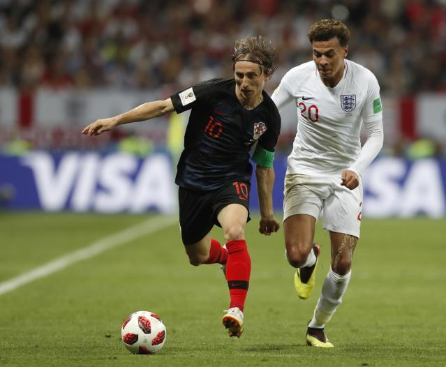 Croatia's Luka Modric, left, and England's Dele Alli challenge for the ball during the semifinal match between Croatia and England at the 2018 soccer World Cup in the Luzhniki Stadium in, Moscow, Russia, Wednesday, July 11, 2018. (AP Photo/Alastair Grant)