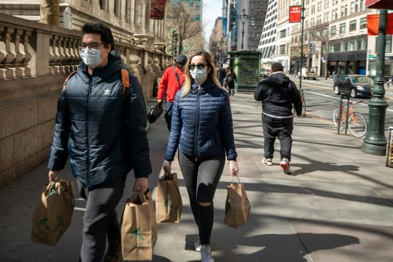 People carry groceries in New York City while wearing face masks and gloves on March 14 (AFP Photo/David Dee Delgado)