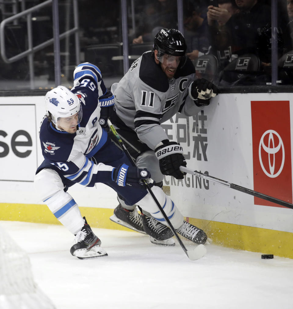 Los Angeles Kings' Anze Kopitar, right, is defended by Winnipeg Jets' Mark Scheifele (55) during the first period of an NHL hockey game Saturday, Nov. 30, 2019, in Los Angeles. (AP Photo/Marcio Jose Sanchez)
