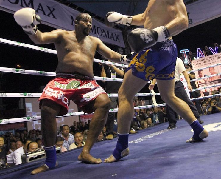 Former heavyweight boxing champion Riddick Bowe of the U.S., left, looses his balance after getting a kick from Levgen Golovin of Russia, right, during their WBC & WMC Muay Thai or Kick Boxing Super Heavyweight Championships fight in Pattaya, Thailand Friday, June 14, 2013. Golovin won the fight in a second round knockout. (AP Photo/Apichart Weerawong)