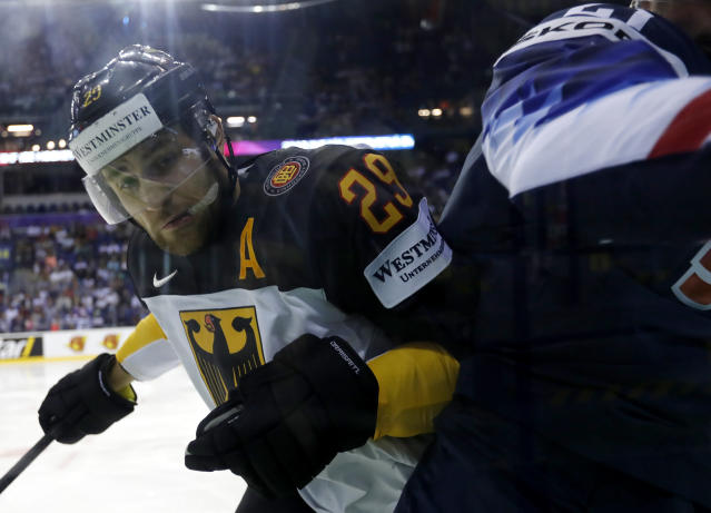 Germany's Leon Draisaitl, left, checks Dylan Larkin of the US, right, during the Ice Hockey World Championships group A match between Germany and the United States at the Steel Arena in Kosice, Slovakia, Sunday, May 19, 2019. (AP Photo/Petr David Josek)