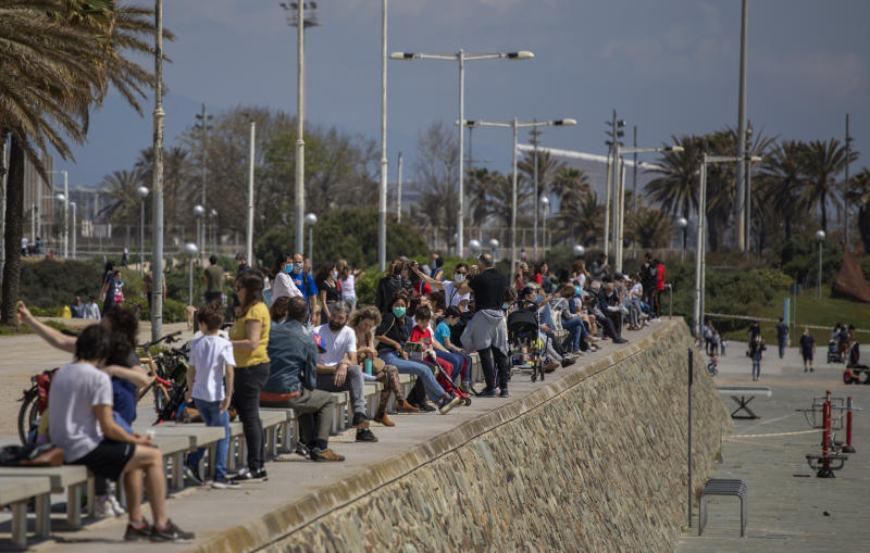 Families with their children sit in a boulevard as police patrol the beach, where access is prohibited, in Barcelona, Spain, Sunday, April 26, 2020 as the lockdown to combat the spread of coronavirus continues. On Sunday, children under 14 years old will be allowed to take walks with a parent for up to one hour and within one kilometer from home, ending six weeks of compete seclusion. (AP Photo/Emilio Morenatti)