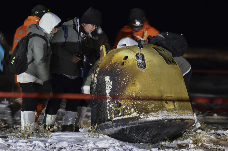 In this photo released by Xinhua News Agency, recovery crew members check on the capsule of the Chang'e 5 probe after its successful landed in Siziwang district, north China's Inner Mongolia Autonomous Region on Thursday, Dec. 17, 2020. A Chinese lunar capsule returned to Earth on Thursday with the first fresh samples of rock and debris from the moon in more than 40 years. (Ren Junchuan/Xinhua via AP)