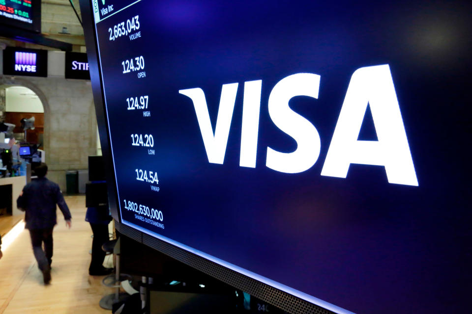 FILE- In this April 23, 2018, file photo, the logo for Visa appears above a trading post on the floor of the New York Stock Exchange. The Department of Justice sued payment processing giant Visa Inc. on Thursday, Nov. 5, 2020, to block the company's purchase of financial technology startup Plaid, calling it a monopolistic takeover of a potential competitor to Visa's ubiquitous payments network. (AP Photo/Richard Drew, File)