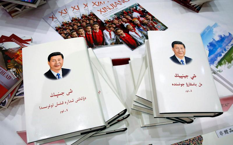 Copies of the book on the governance of Chinese President Xi Jinping are displayed with booklets promoting Xinjiang during a press conference by Shohrat Zakir, chairman of China's Xinjiang Uighur Autonomous Region - AP