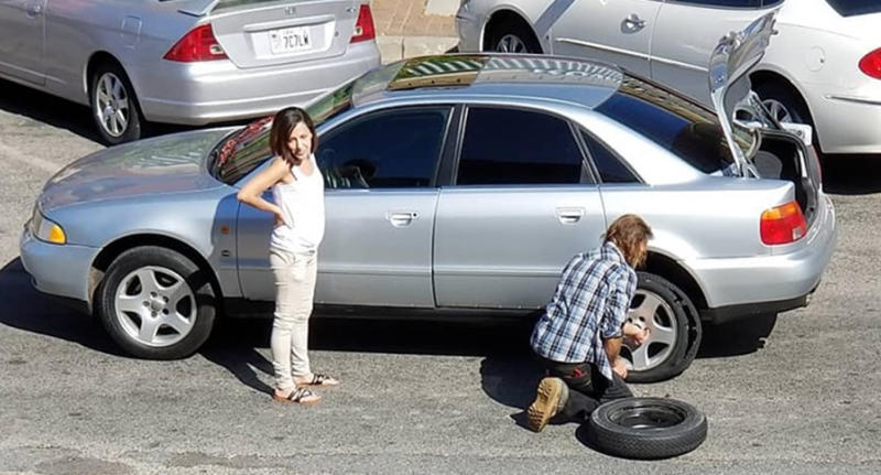 Utah homeless man Chuck helps a woman with her blown-out tyre on her car.