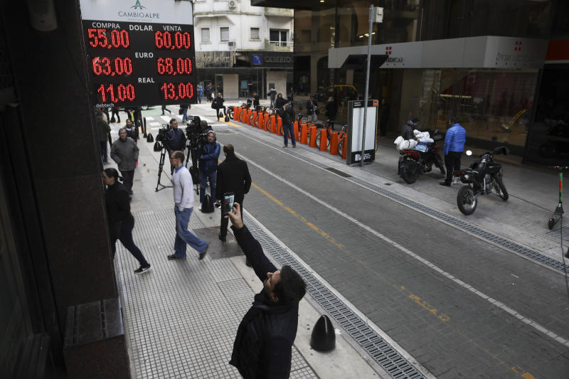 A man takes a photo of the exchange rate displayed on a currency exchange board in Buenos Aires, Argentina, Monday, Aug. 12, 2019. The peso devalued sharply on Monday in Argentina after a striking victory by the opposition in Sunday's presidential primaries ahead of October's presidential elections. (AP Photo/Natacha Pisarenko)