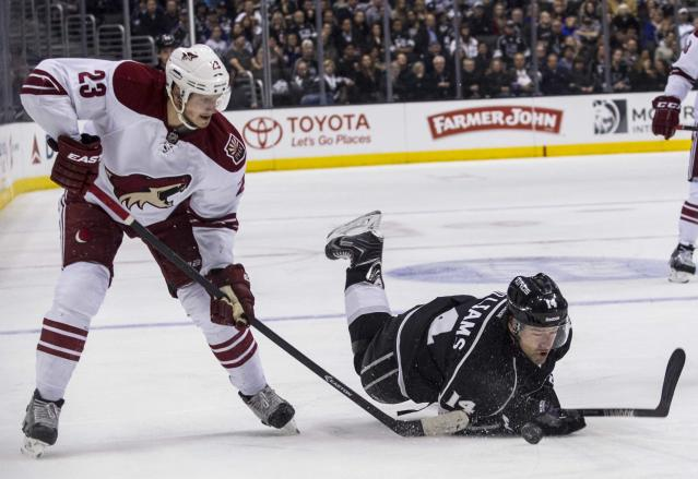 Los Angeles Kings forward Justin Williams (14) falls as Phoenix Coyotes defenseman Oliver Ekman-Larsson (23) steals the puck during the second period of an NHL hockey game, Wednesday, April 2, 2014, in Los Angeles. (AP Photo/Ringo H.W. Chiu)