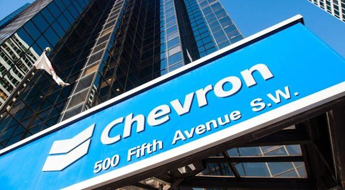 Chevron (CVX) logo on blue sign in front of skyscraper building