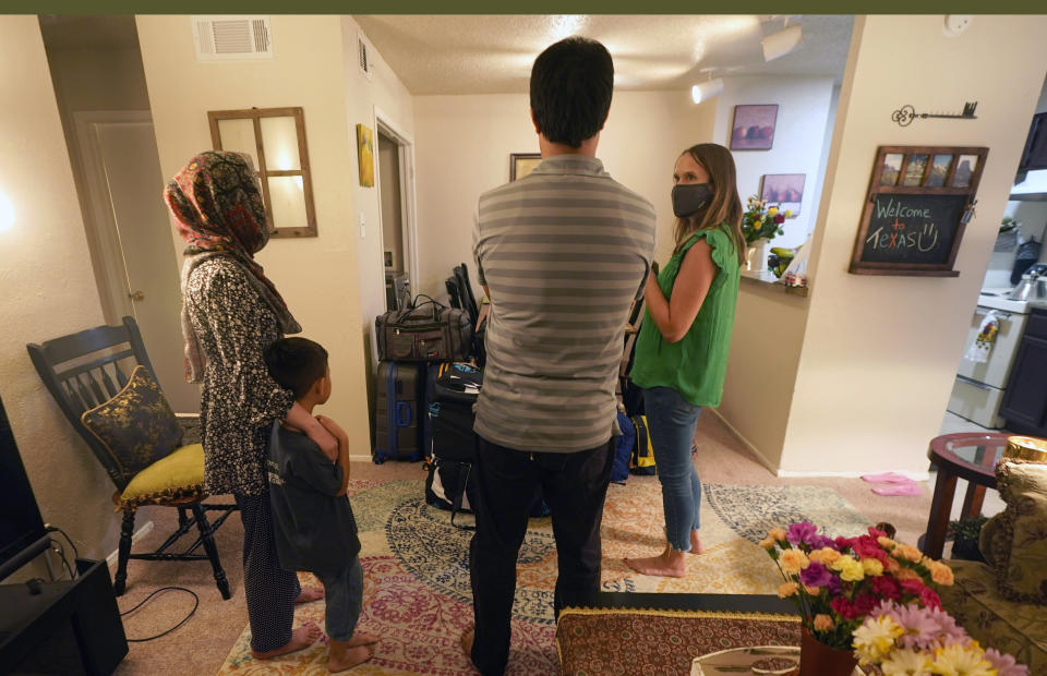 On their first day in a new apartment, a family that fled Afghanistan three weeks ago speaks with Megan Carlton, right, with the Refugee Services of Texas at their new home in Dallas, Tuesday, Aug. 17, 2021. The father worked as an interpreter in Afghanistan and the family did not wish to be identified in the photos. (AP Photo/LM Otero)