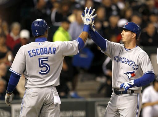 Toronto Blue Jays' David Cooper, right, celebrates his two-run home run with Yunel Escobar, off Chicago White Sox starting pitcher Philip Humber, after the pair scored during the fifth inning of a baseball game Tuesday, June 5, 2012 in Chicago. (AP Photo/Charles Rex Arbogast)