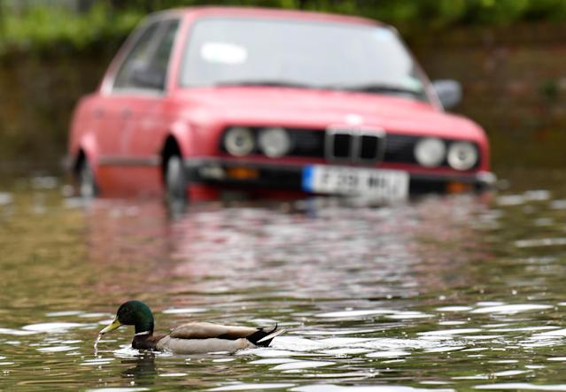 A duck paddles past a car parked along a flooded street adjacent to the Thames after the river burst its banks following heavy rain in London, Britain, April 30, 2018. REUTERS/Toby Melville