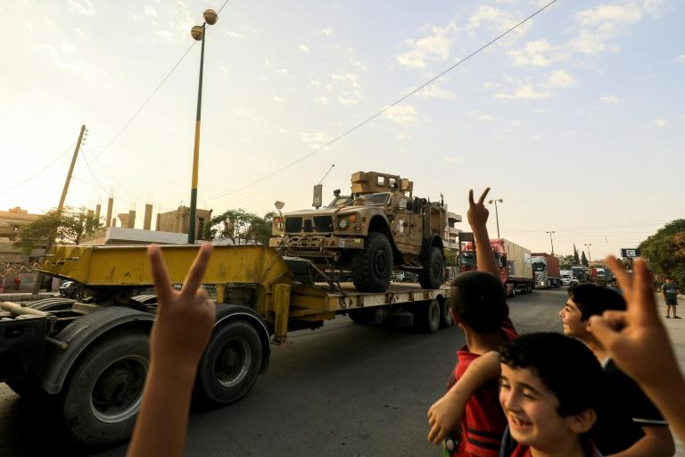 Children flash victory signs as a convoy carrying US-made Oshkosh armoured vehicles heads to the Syrian city of Raqa on September 19, 2017 to reinforce fighters of the Syrian Democratic Forces battling the Islamic State group in its onetime bastion