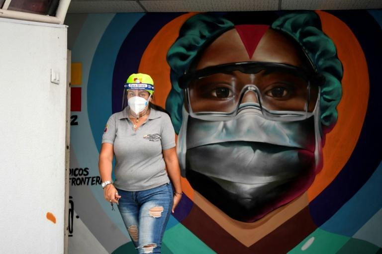 An employee passes before a mural on the wall of a Caracas hospital honoring the efforts of healthcare workers against Covid-19; Facebook has banned Venezuela's president Nicolas Maduro for a month for posting Covid misinformation