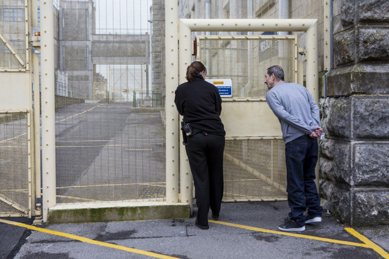 A prisoner accompanied by an officer walking through the prison to visits. HMP/YOI Portland, Dorset. A resettlement prison with a capacity for 530 prisoners. Portland, Dorset, United Kingdom. (Photo by In Pictures Ltd./Corbis via Getty Images)